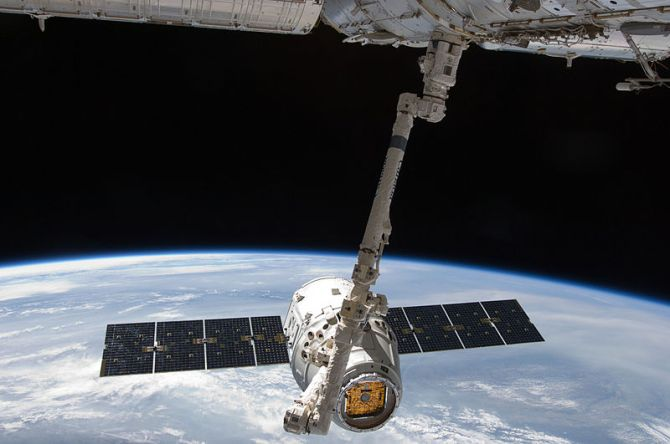 SpaceX Dragon commercial cargo craft is grappled by Canadarm2 at the ISS